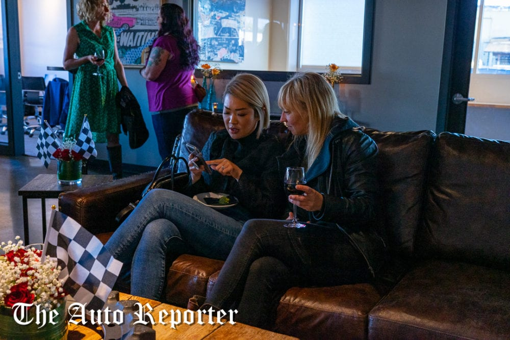 One woman shows another something on her phone during the Beauty & Key's launch at The Shop - The Auto Reporter