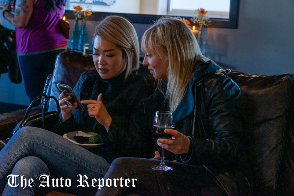 Two ladies look at a phone during Beauty & Key's launch at The Shop - The Auto Reporter