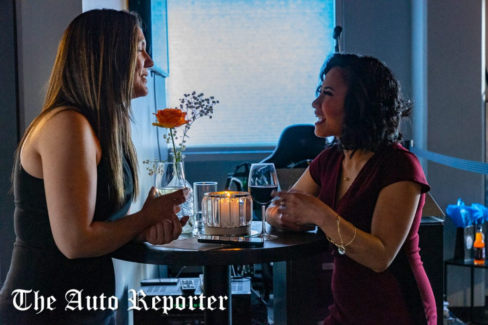 Two ladies, one from BMW Seattle, chat at the Beauty & Key's launch at The Shop - The Auto Reporter